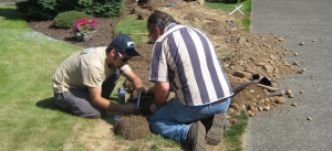 two irrigation repair pros are in the middle of a broken pipe fix